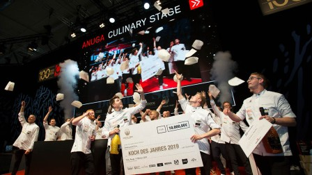 All cooks are assembled on stage and throw their toques into the air. The winners are holding a big check.