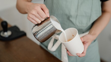 Barista pours coffee in a paper cup