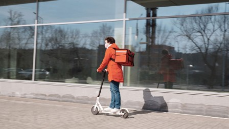 Man delivering food on an e-scooter