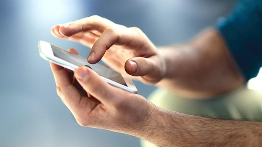 Eine Person hält ein Handy in der Hand und bedient es mit der anderen
