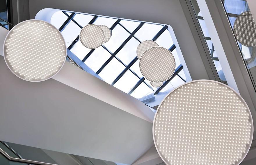 Lichtdurchflutetes Atrium mit den abgependelten Modul R Project Leuchten von unte